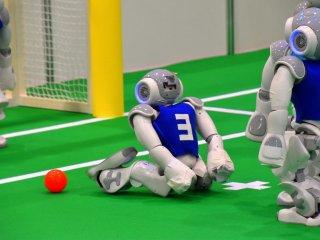 Robot No. 3 tim Taiwan mencoba menendang bola ke tujuan dan jatuh ke punggungnya