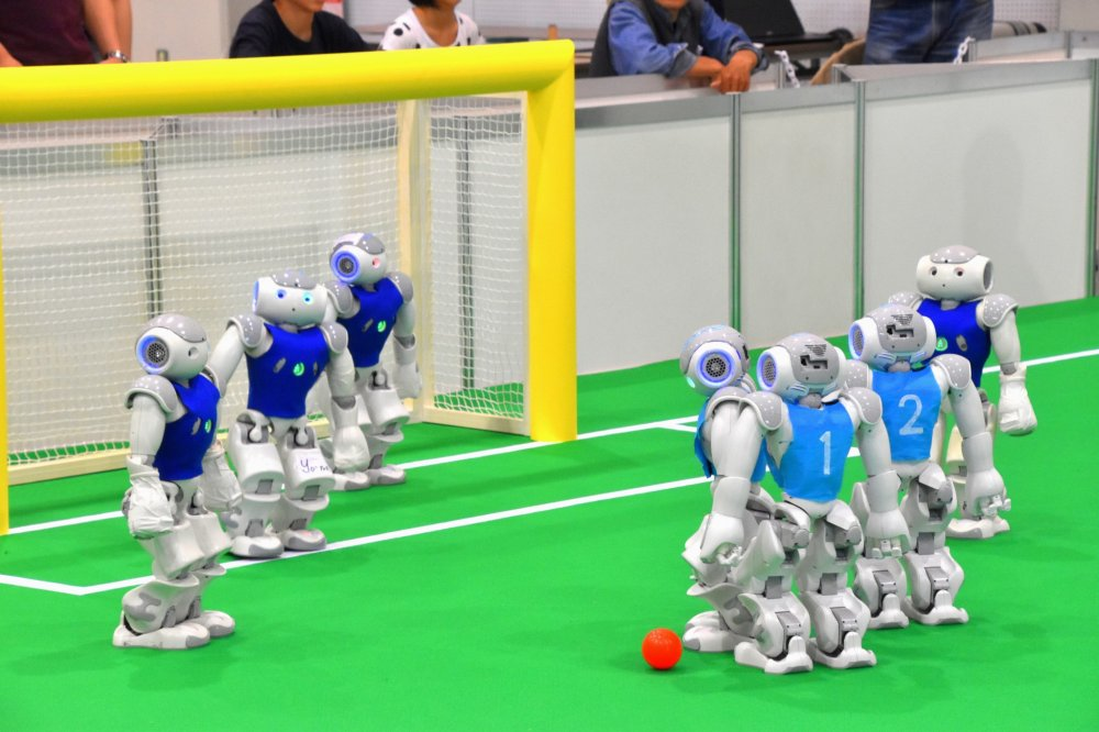 Robot otonom yang berbentuk manusia bermain sepak bola. Para humanoid yang mengenakan seragam biru tua milik Crude dari Taiwan, dan yang mengenakan seragam biru langit adalah JoiTech dari Universitas Osaka.