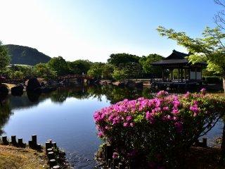 紫式部公園の寝殿造り庭園の池と釣殿。この公園は背後の山を借景している。