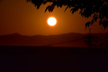 The huge round-shaped sun setting over a mountain
