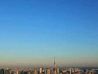Tokyo Tower beneath a mid day moon