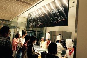 """A loja de """"take-away"""". Muitas pessoas estavam a comer gelado e """"baumkuchen sablé""""."""