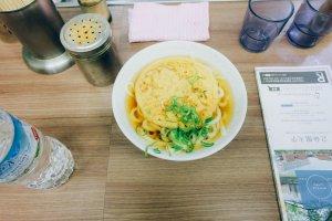 Semangkuk besar Tenpura Udon dengan daun bawang yang banyak disajikan panas-panas. Tambahkan bubuk cabai agar rasanya semakin mantap!
