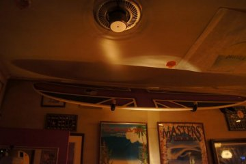 The walls and ceiling are adorned with surf memorabilia