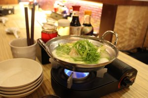 The gyoza dumplings in white soup are cooked on your table