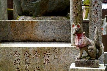 <p>수없이 많이 보이는 여우석상 중 하나. 오래된 듯 석상을 두른 붉은 두건도 빛바래 있었어요.</p>