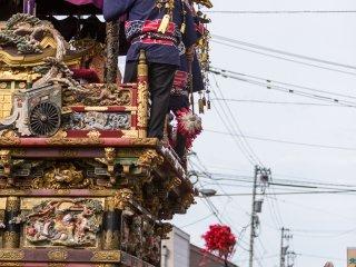 Six chars en bois, datant de l'époque d'Edo,défilent à travers la foule