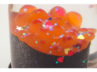 A close up as the glitter falls on the salmon egg roe.