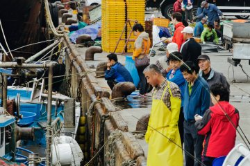 <p>Market traders scanning newly arrived boats</p>