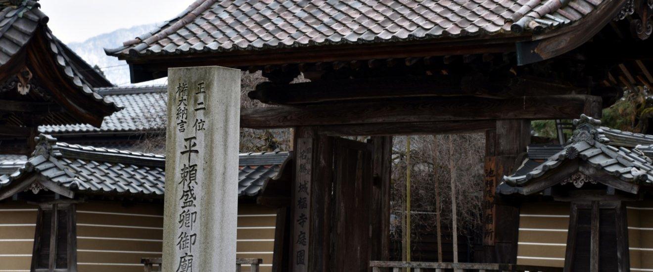 城福寺山門。平清盛の異母弟、源頼朝の命を救った池禅尼の実子、平頼盛の廟所を表わす石碑が建っている。