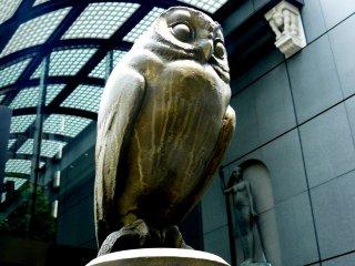 Сова охраняет вход в здание справа, а вдали виднеется мифическое существо в роли Атланта