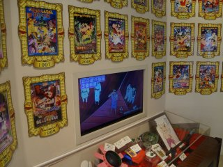 "The wall of Shin-chan, an ode to the 23 Crayon Shin-chan films with a display case of ""props"" underneath."