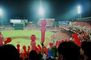 """Les fans des Hiroshima Carp lâchant leurs ballons pour la 7e manche au stade Mazda """"Zoom Zoom""""."""