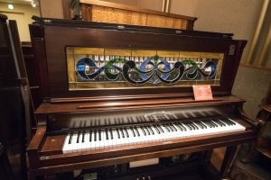 This is no piano. Behind the panel lies the musical box which not only plays the tunes, but also engages the keyboards, making it look like the 'piano' is being performed on.
