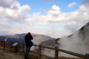 山的山腰中有一个喷烟口,可以看到几条白烟从裂缝中飘起