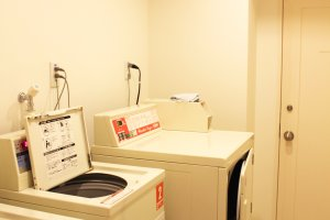 The laundry room has two washing machines and a dryer.