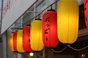 Distinctive red and yellow lanterns that welcome you to Kushikatsu Tanaka
