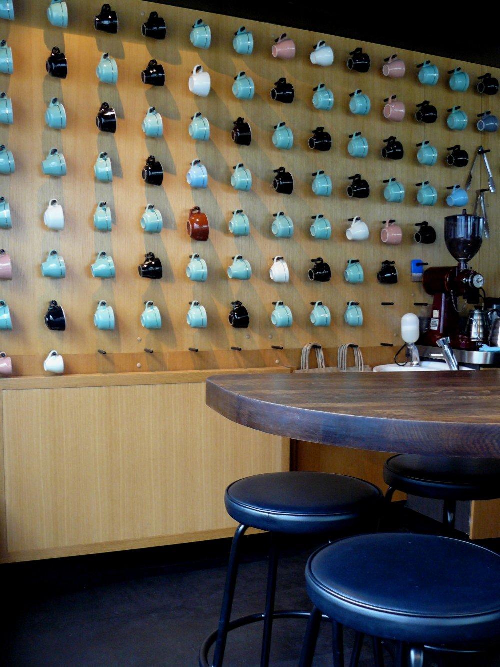 На стене много чашек разного цвета, и их можно разглядывать, пока ждешь заказ