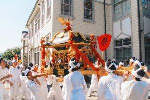 ผู้คนแบก Mikoshi ไว้บนไหล่ขณะกำลังเดินผ่านช่วง Bikan ในประวัติศาสตร์แห่งยุคเอโดะ