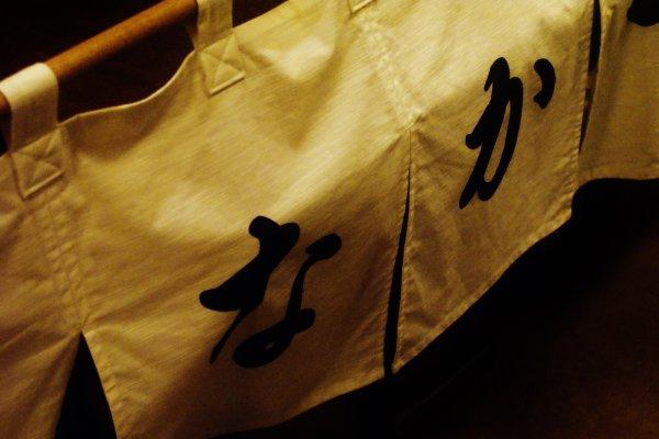 Le nom de l'izakaya est dessiné sur des drapés à l'intérieur du magasin