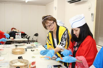 <p>The instructor helping a student and demonstrating how to hold the rice and fish</p>
