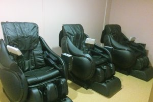 Three massage chairs outside of the onsen