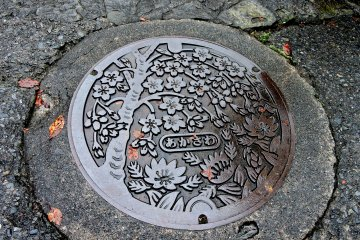 Akasawa-juku's manhole cover features cherry blossoms and another spring flower