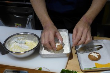 <p>The chef demonstrates how to coat the tempura ingredients before cooking.</p>