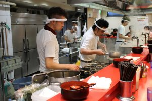 Chefs hard at work preparing a dozen ramen servings at once.