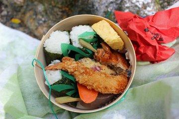<p>The lunch&nbsp; bento, three onigiri rice balls, vegetable and shrimp tempura, chicken kushiyaki (Japanese chicken skewer), egg and konyaku</p>