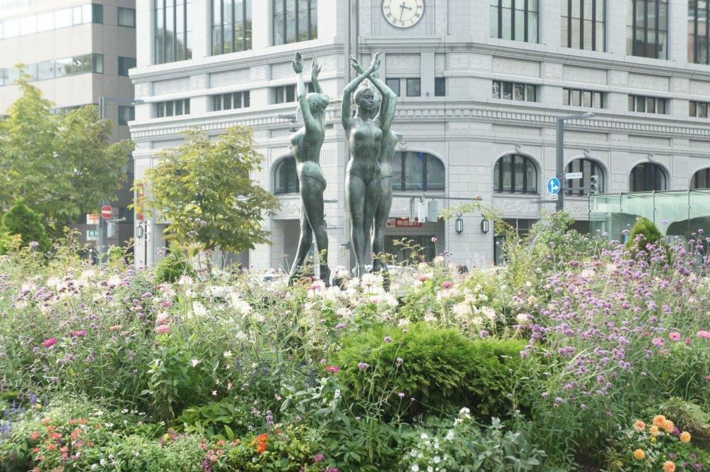 Tak mengira ini Jepang ya? Bunga-bunga cantik, patung penari, dengan latar bangunan khas Eropa di Taman Oodori.