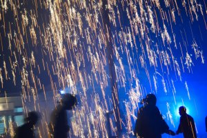 Running around beneath the blow tube fireworks as they rain down sparks.
