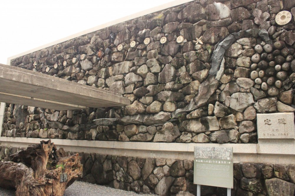 At the back of the monument is a stone wall designed by Architect Kenji Imai, depicting the month-long pilgrimage of the 26 Martyrs from Kyoto to Nagasaki.