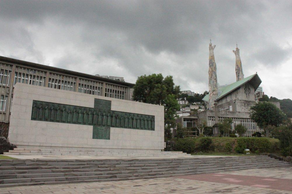 Слева: гранитно-бронзовый памятник 26 мучеников Японии, все мученически погибли на холме Нисидзака в Нагасаки 5 февраля 1597 года. Этот памятник был создан профессором Ясутакэ Фунакоси. За ним находится музей, посвященный 26 мученикам и истории христианства в Японии. Справа: церковь Св. Филиппа. Посвященный святому Филиппу Иисусу, 24-летнему мексиканцу, который был первым из 26, кто ушел.