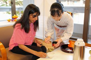 The main teacher instructs a guest in measuring and preparing tea