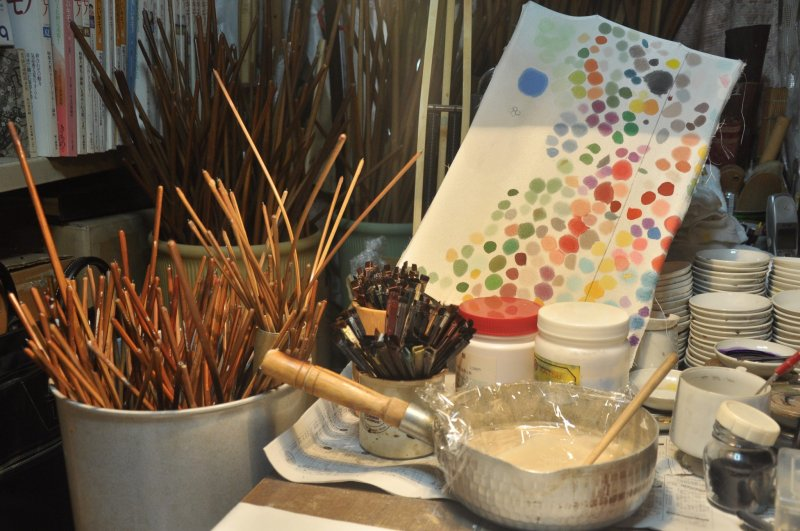 <p>Wooden sticks, used to frame up a piece of cloth, glue and paintbrushes are readily available on the table.</p>