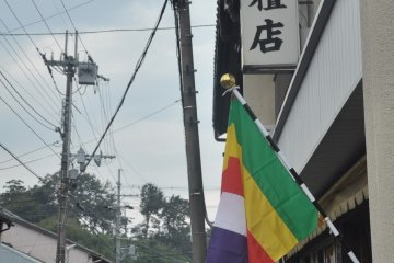 <p>The coloured flag relates to Buddhism</p>