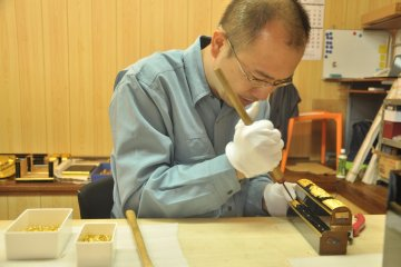 <p>A crafstmen works with metal that&#39;s used to decorate the Buddhist altars</p>