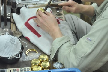 <p>A goldsmith is etching intricate patterns into small vessels</p>