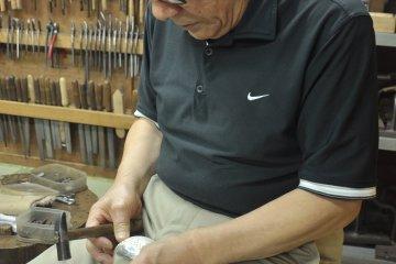 <p>Ishiguro performs&nbsp;Tama-arare, his signature etching patterns</p>