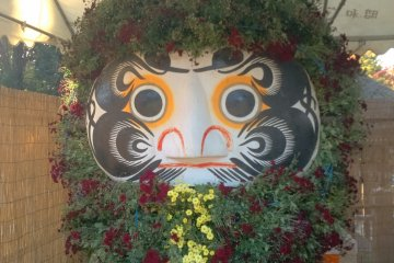A Daruma doll decorated with leaves and flowers