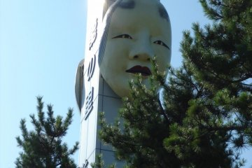 Statue of Noh mask by the terminal building in Ryotsu Port