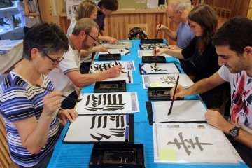 <p>Visitors from Australia and France try their hand at shodo</p>