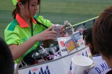 A beer vendor busy keeping the thirsty fans happy.