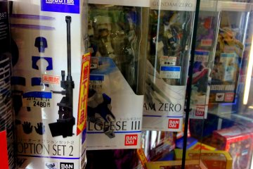 <p>Several action figures are on glass display</p>