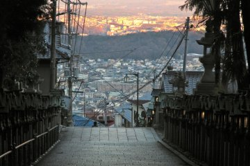 <p>The buildings and homes of Nara and Ikoma Cities glow fiery orange in the sunset before being swallowed by the shadow of Mt. Ikoma</p>