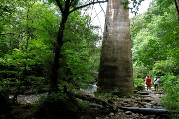 Tall pylons of a rail bridge across the stream tower over sightseers walking the trail