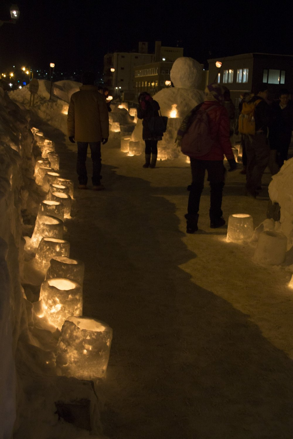Candlelit path leading to a giant snowman