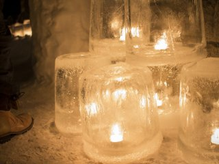 Candles are encased in ice, lighting the path