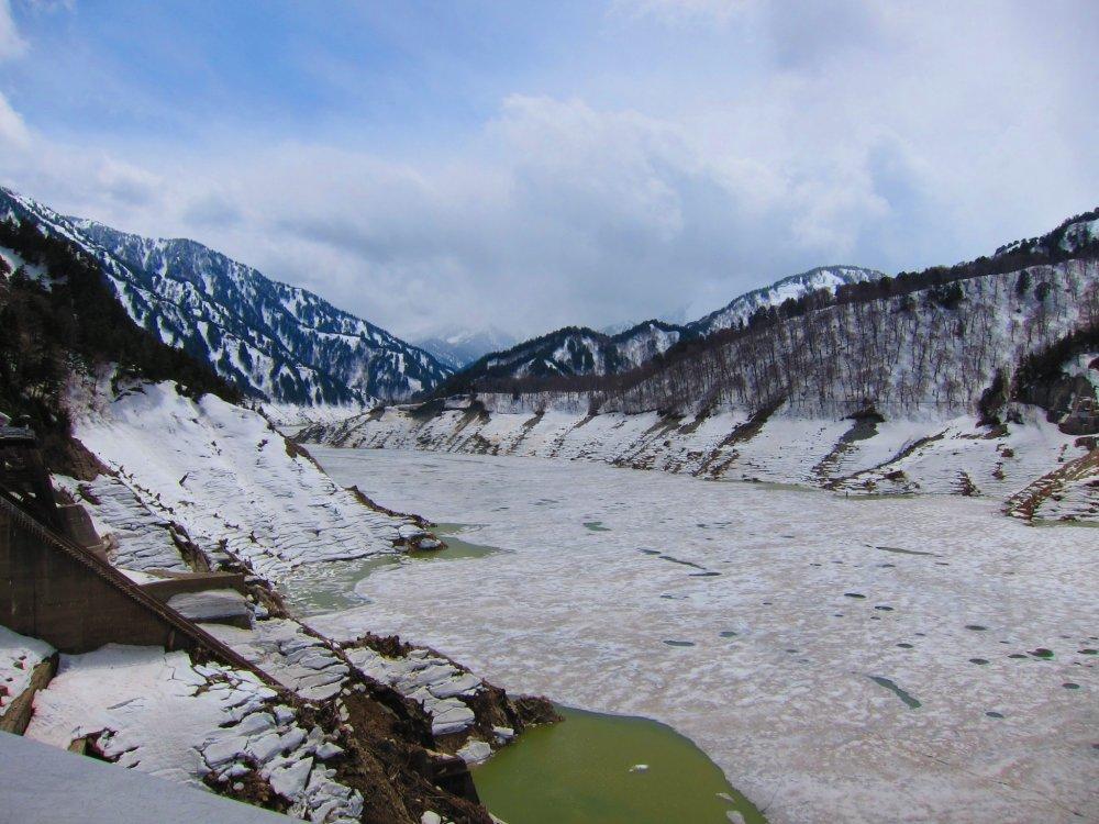 A majestic scene of the Kurobe Lake blanketed in snow